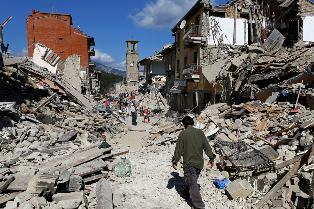 A man walks through rubble between destroyed buildings
