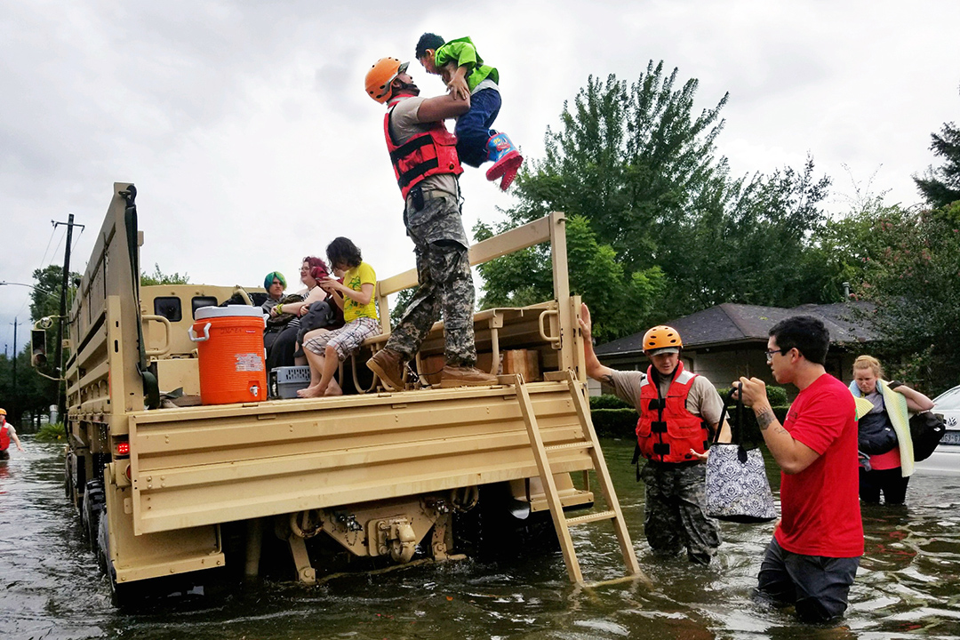 Survivors wade through floodwater while a rescuer lifts a young boy onto a truck