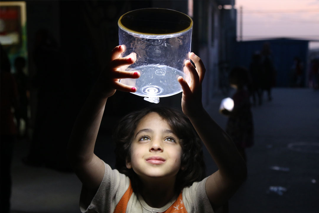 A child smiles while lifting an electric lamp
