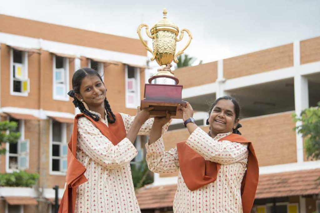 Two smiling women hold a trophy