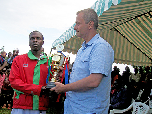 a man awarding a trophy to another man