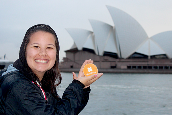 woman with a GlobalGiving sticker in front of the Sydney Opera House