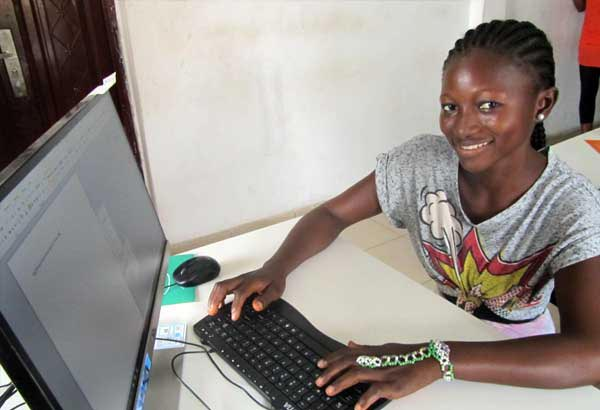 A young woman smiles while using a computer