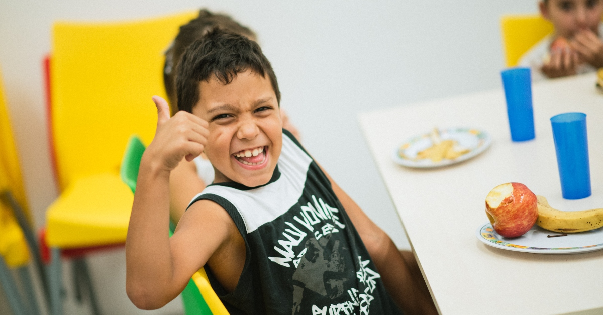 boy smiling at the camera, giving a thumbs up | nonprofit newsletter