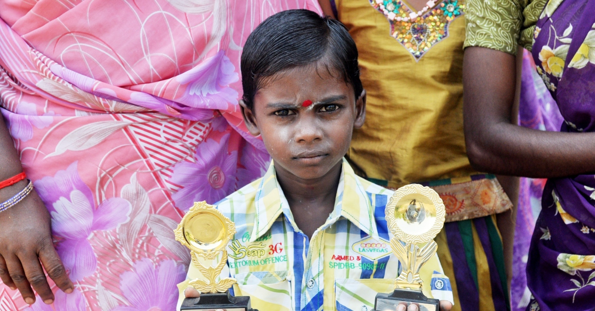 Child holding two trophies. Trust Indicators