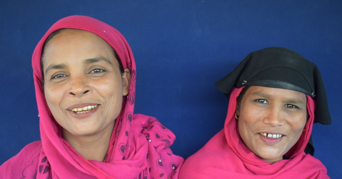 refugees covid-19. two female refugees smiling proudly