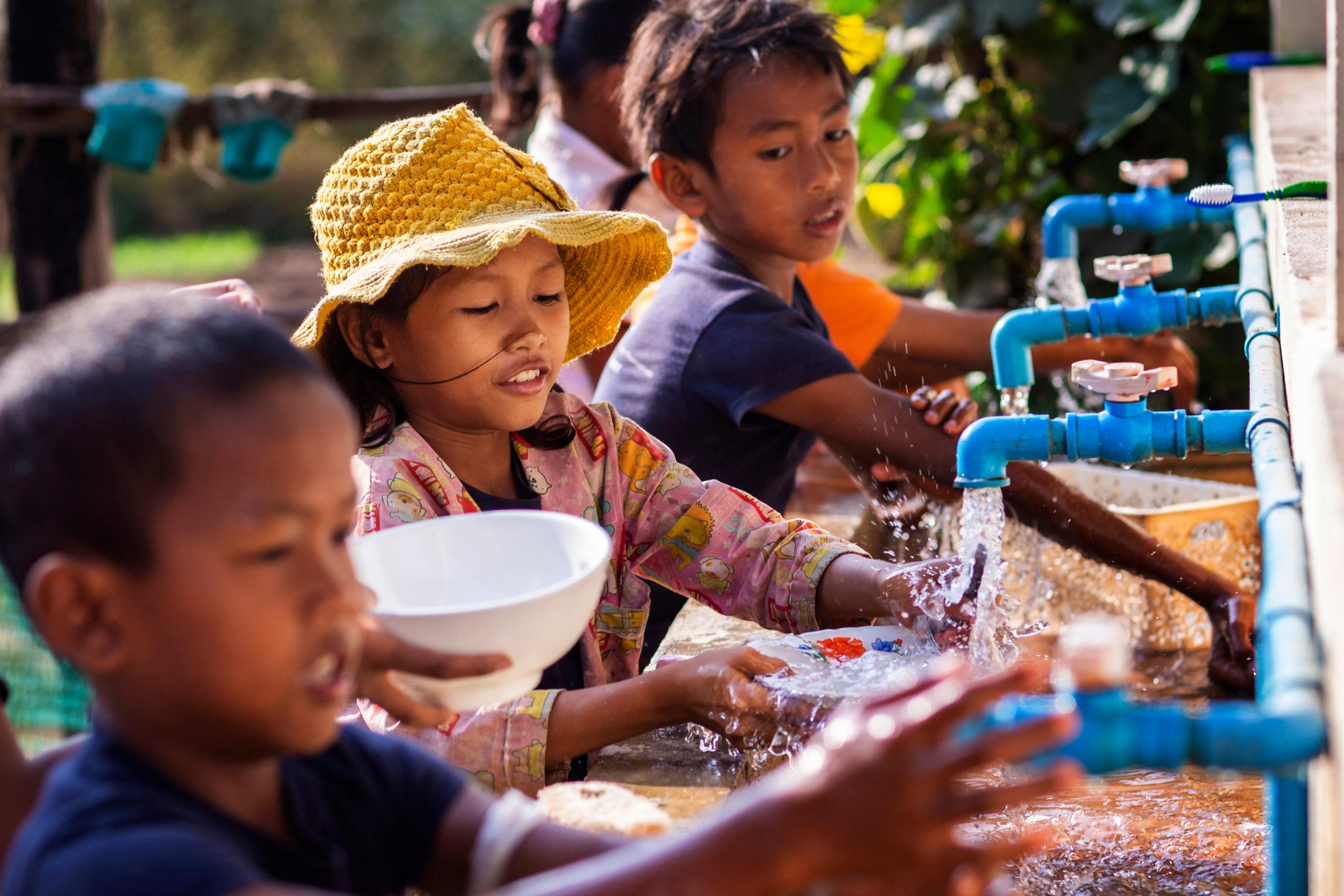 Several children washing bowls together