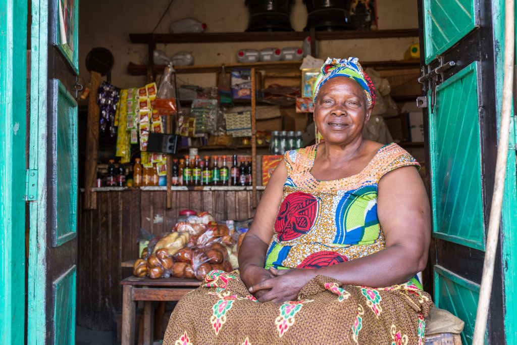 A smiling grandmother, sitting in front of her shop