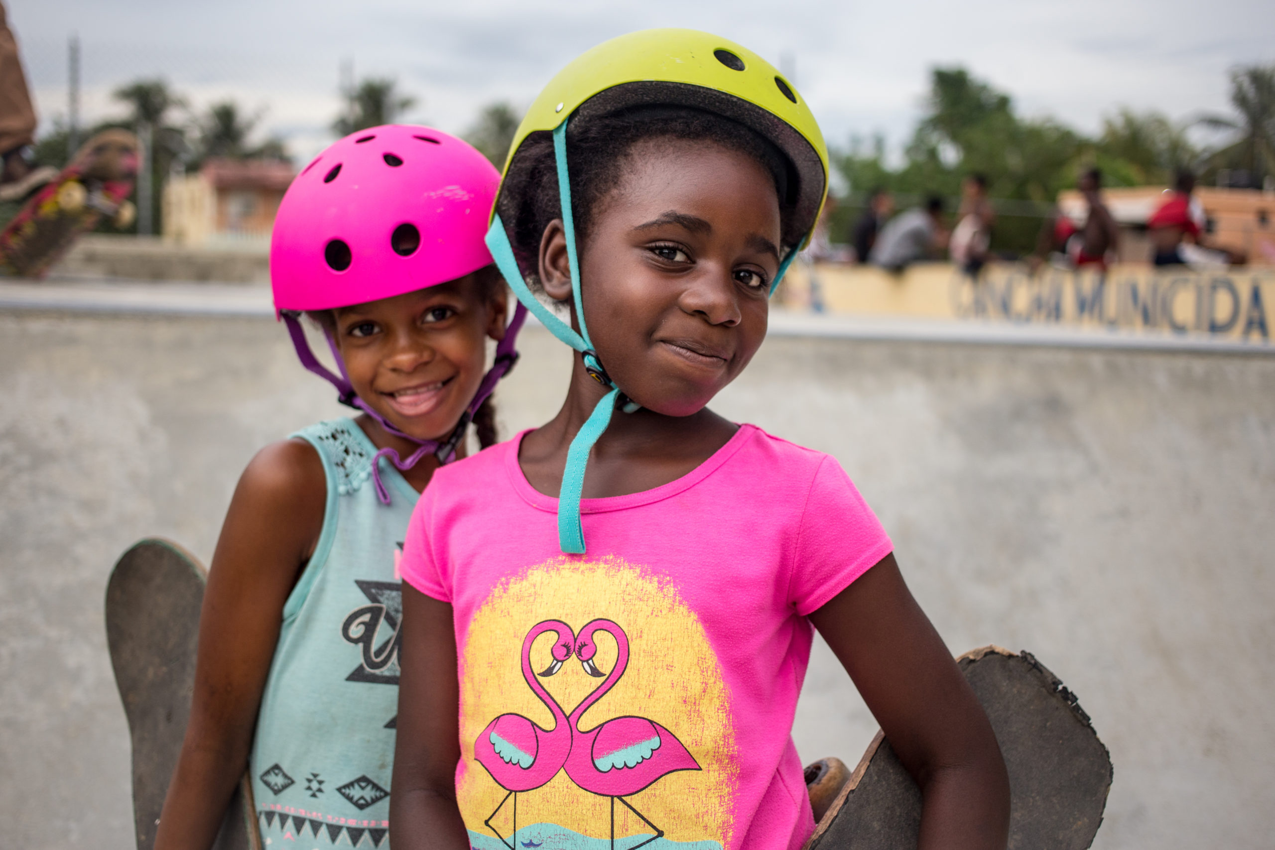 two girls in helmets, smiling and holding their skateboards