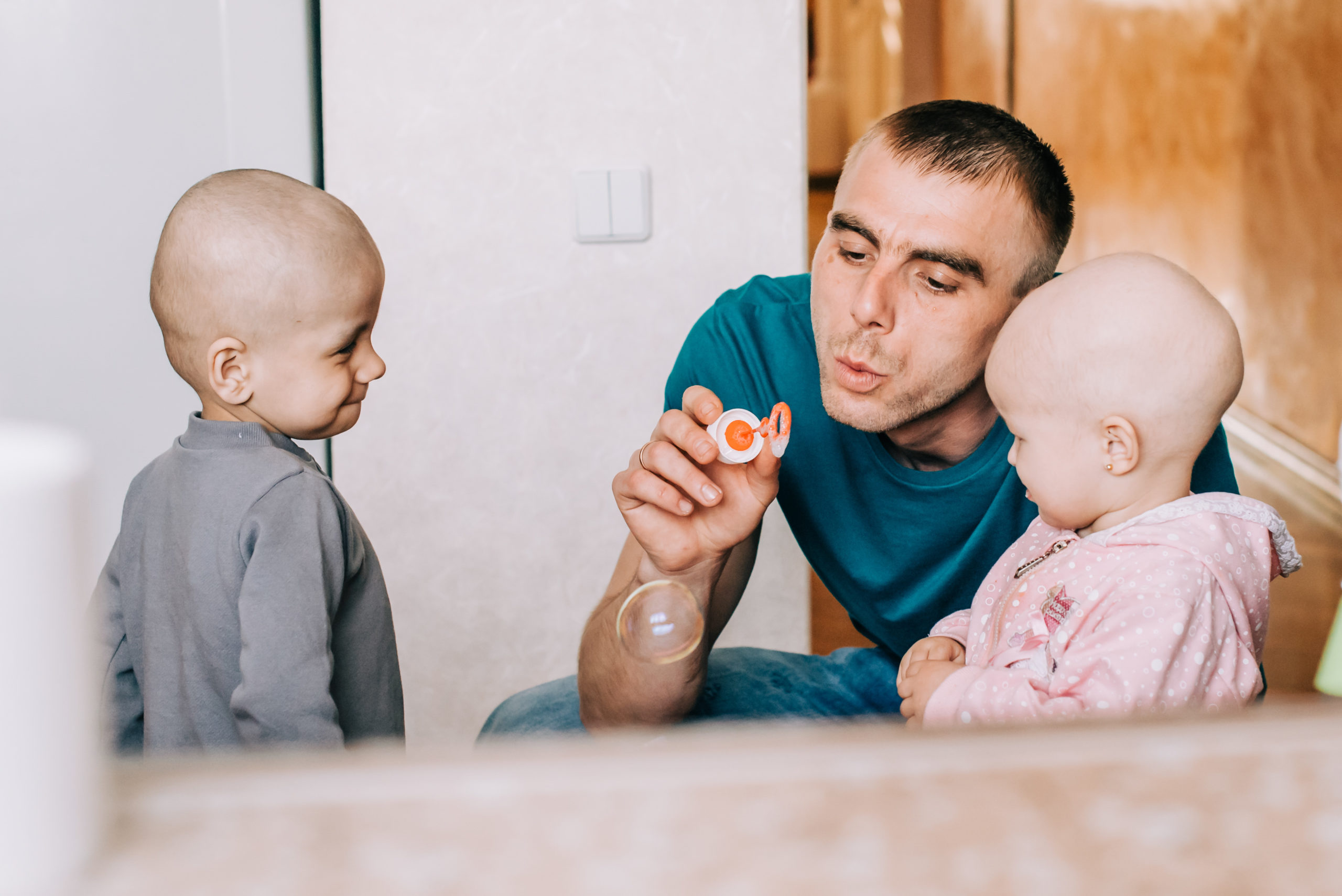 A person blowing bubbles with two small children