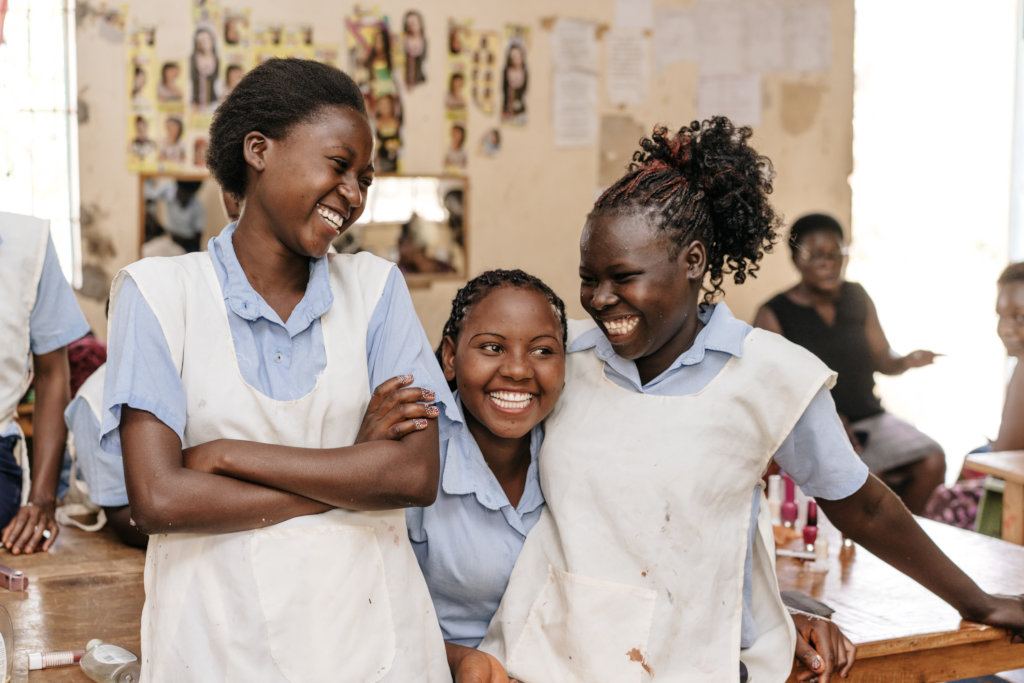 Three girls smiling together in a classroom