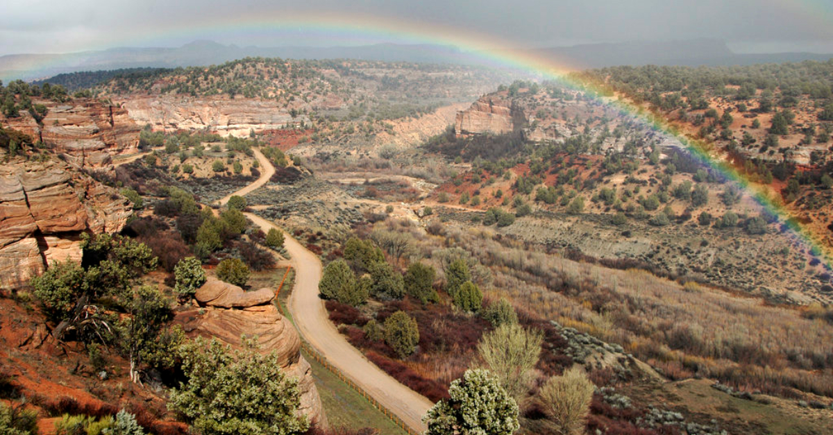 Company ethics. A rainbow stretches over a canyon landscape.