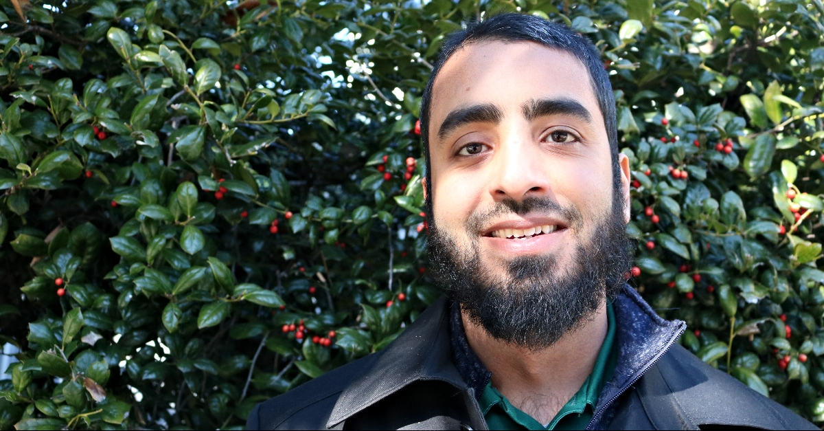 Muhammad Rayhaan stands in front of a green hedge