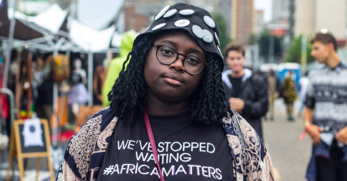 "A woman in a black T-shirt that says ""We've stopped waiting. #AfricaMatters"""