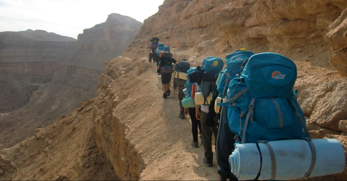 A line of backpackers with blue packs hike near the edge of a cliff