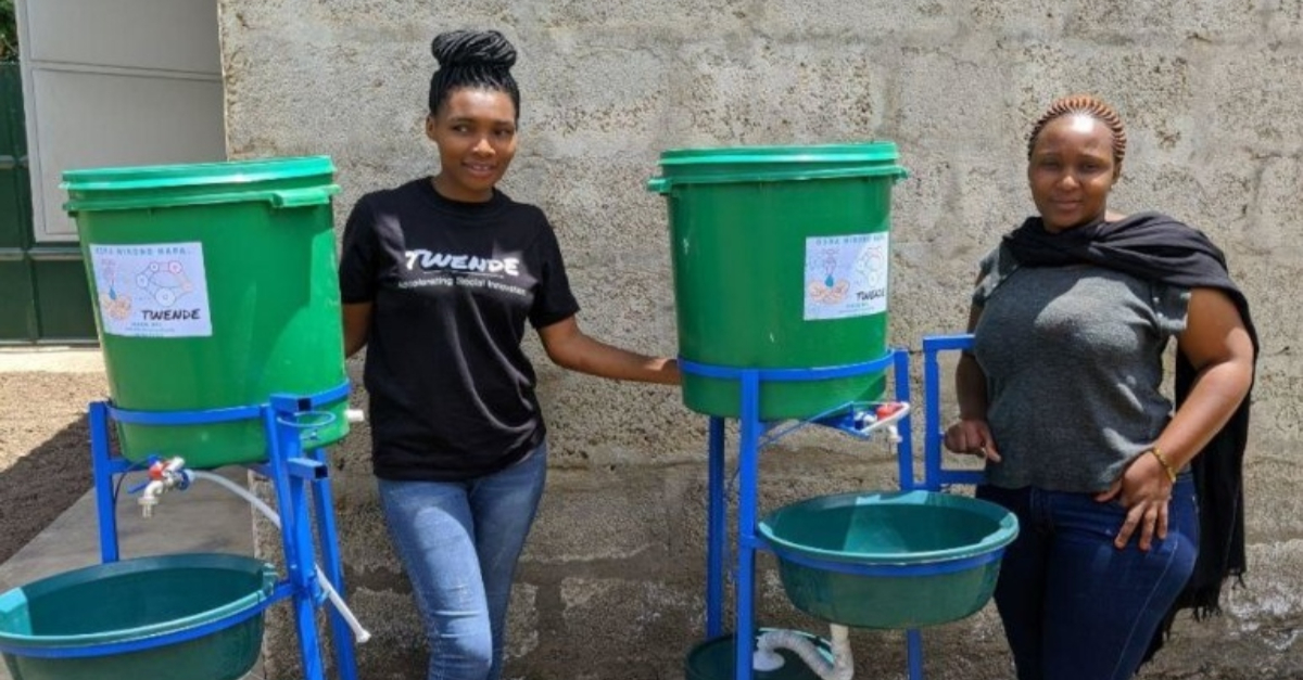 Two women standing in front of a foot-operated hand-washing station. Innovative nonprofit solution