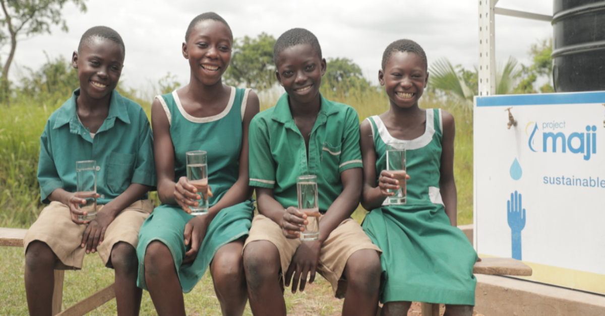 Children drinking clean water from their solar-powered water kiosk in Ghana.