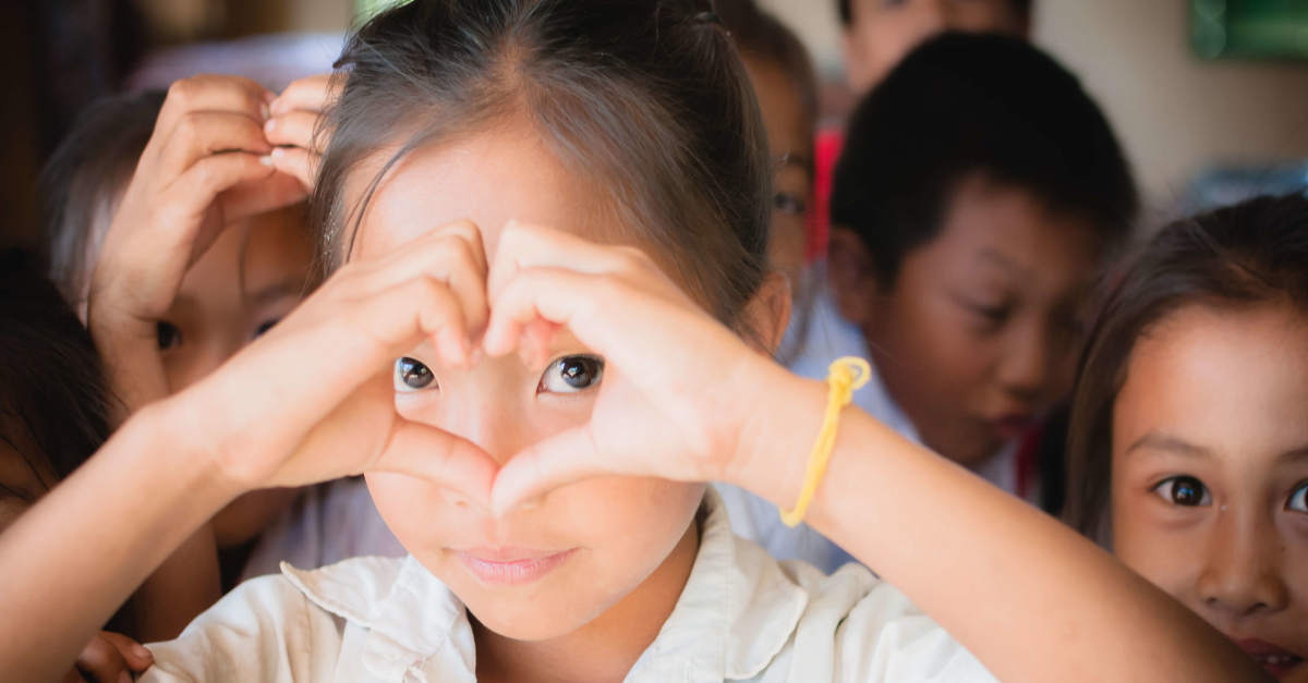 Girl making a heart with her hands. Virtual gift idea for the 2020 holiday season.