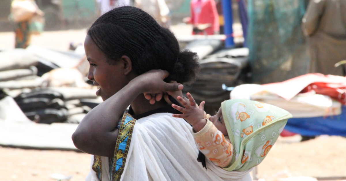 A woman in a white shirt carries her baby on her back in Ethiopia, which is affected by the Tigray crisis.
