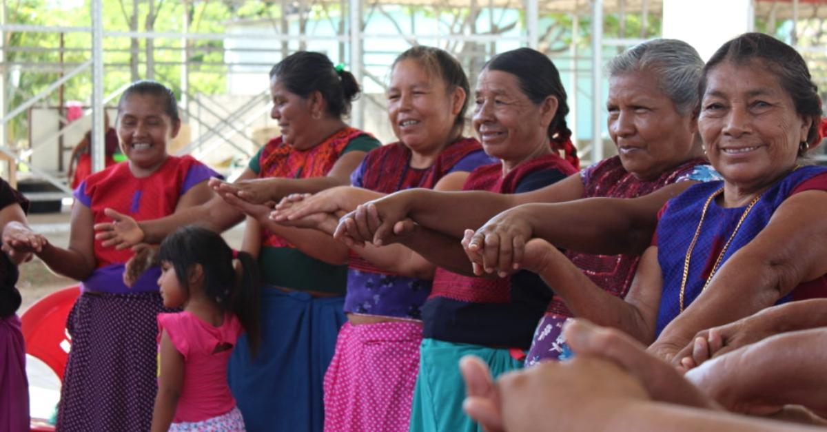 women hold hands in a circle filantropía-liderada-por-la-comunidad