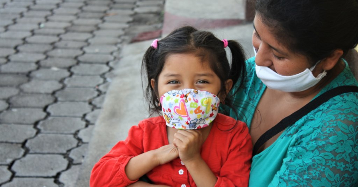 globalgiving's impact in 2020. A woman in a mask and a blue shirt holds a young girl wearing a mask and a red shirt. with her hands clasped below her chin.