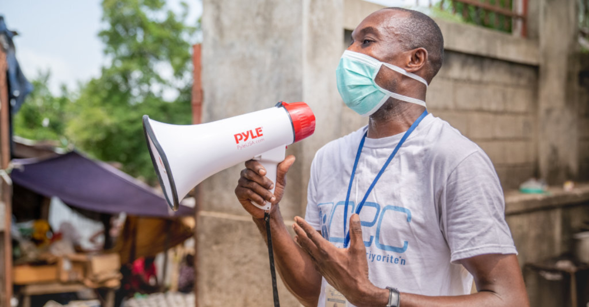A man wearing a blue mask holding a megaphone. Covid-19 complicates disaster response