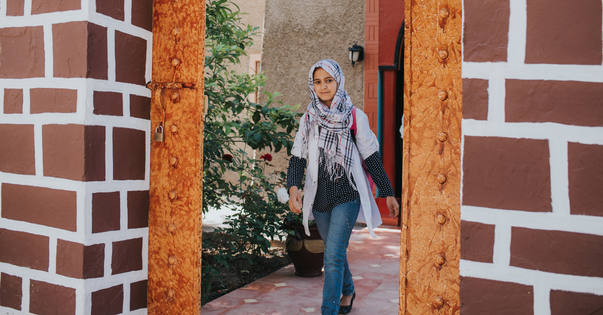 CSR conferences to attend. A girl with a head covering walks toward an entryway