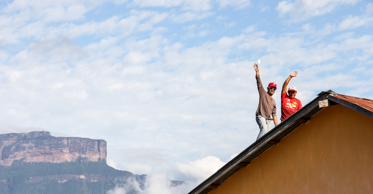 Two men waving hello from the top of a building. GlobalGiving's Year In Review