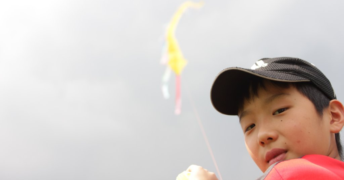 A boy in a black hat holds a yellow kite above his shoulder. iapan-earthquake-tsunami-recovery