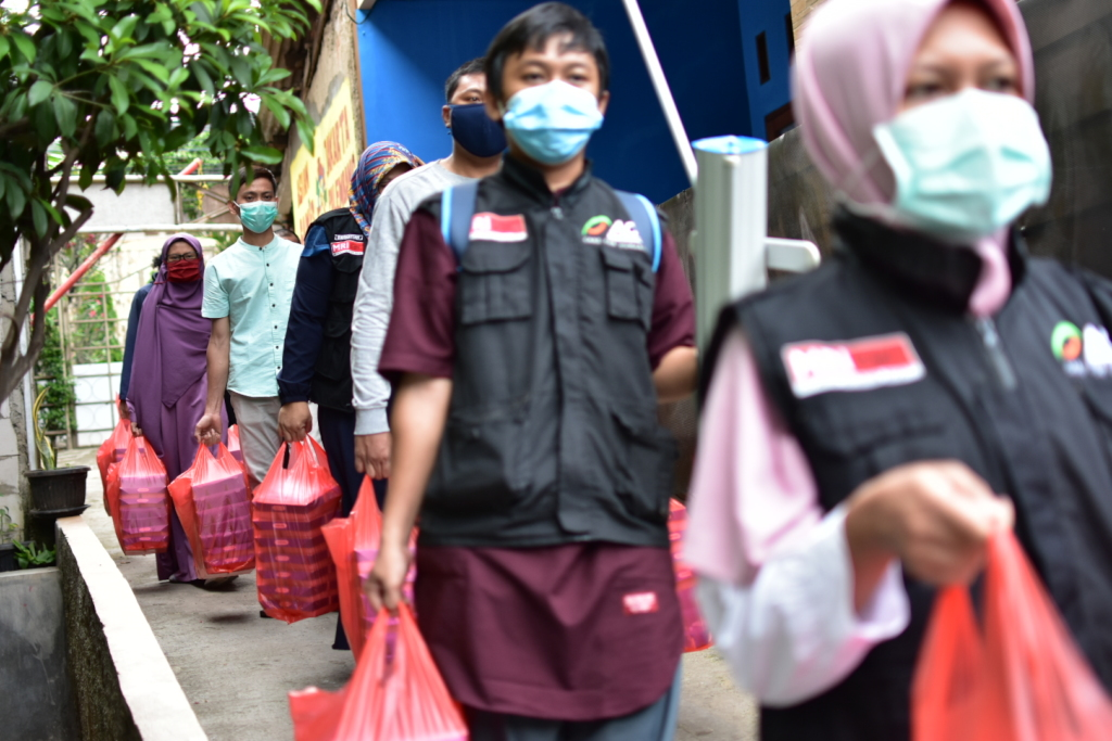 Workers hold red plastics bags with food packages inside