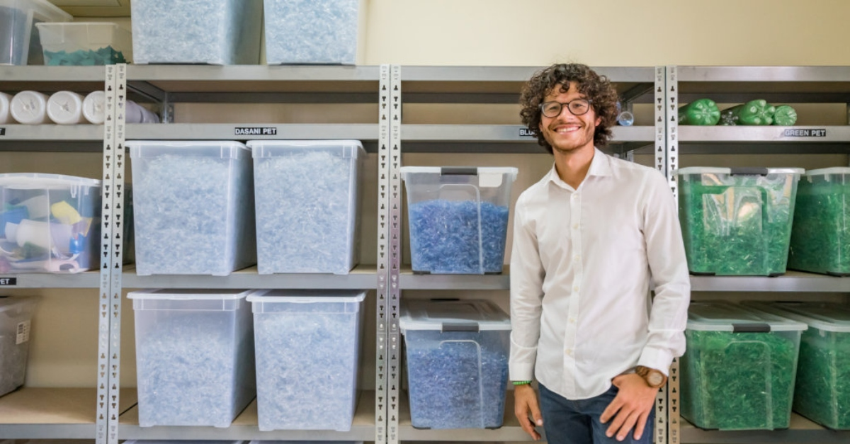 A man in a white shirt stands in front of bins of colored plastic pieces