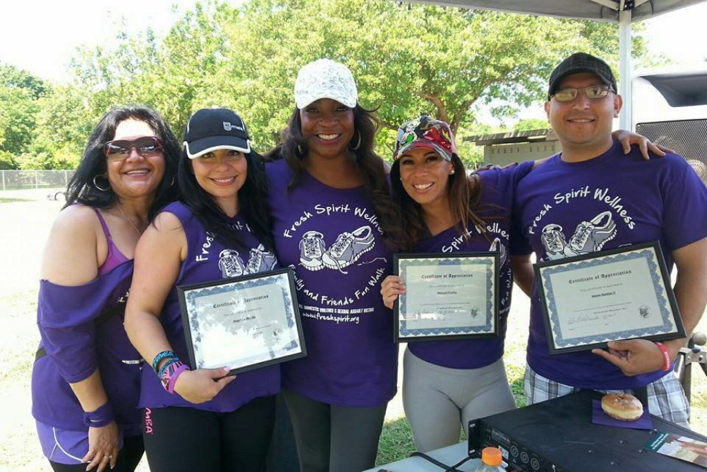 Women stand together holding up certificates of completion for an advocacy walk