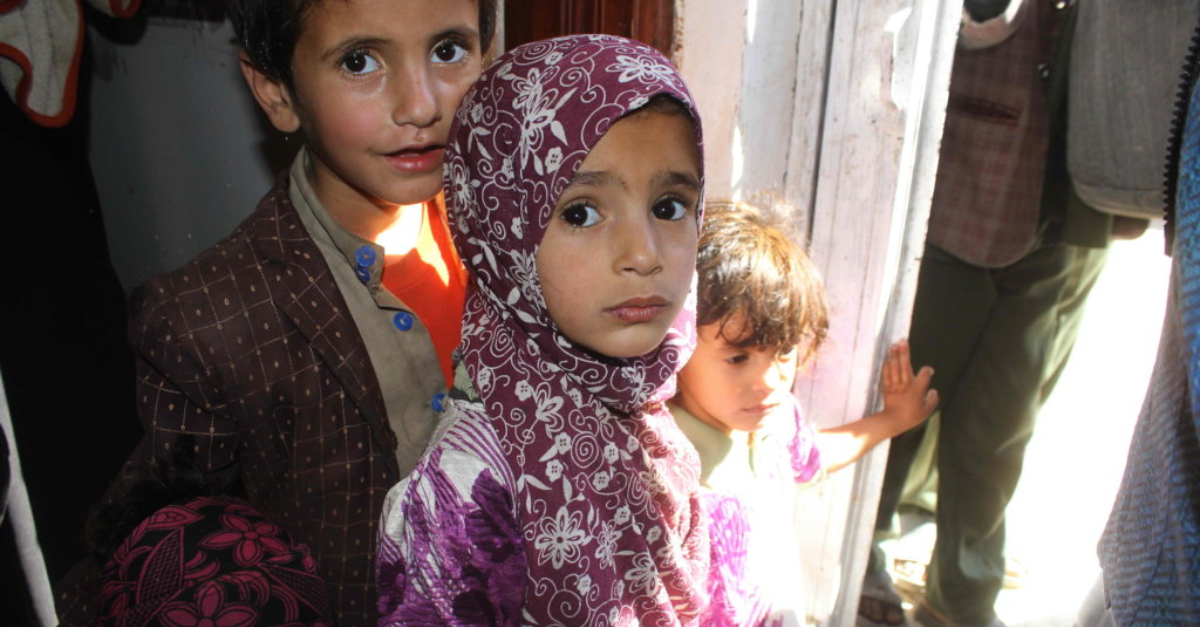 Young children affected by the Yemen crisis stand in a doorway