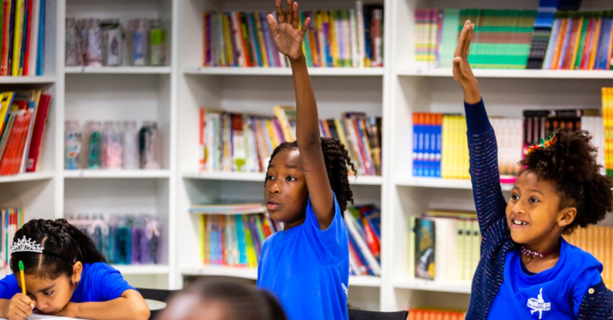 business leaders social change. Girls in blue uniforms eagerly raise their hands in a classroom