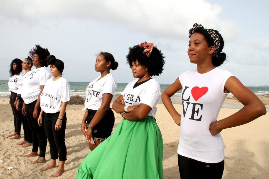 Women stand in a line on a beach looking off into the distance