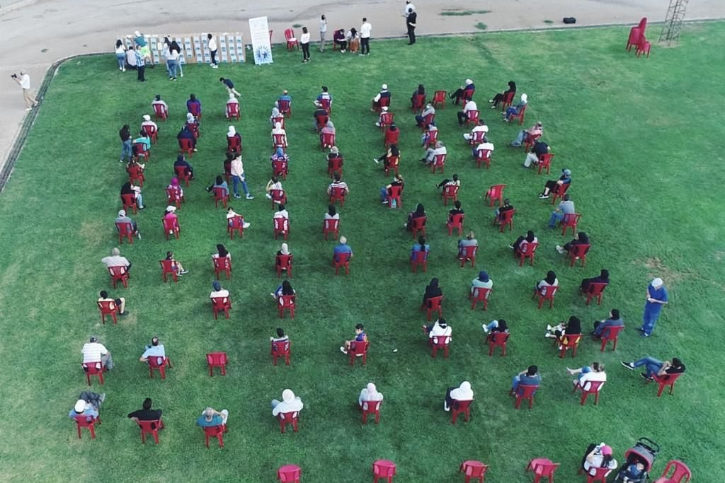 Aerial view of a socially distanced training with rows of attendees seated in red chairs