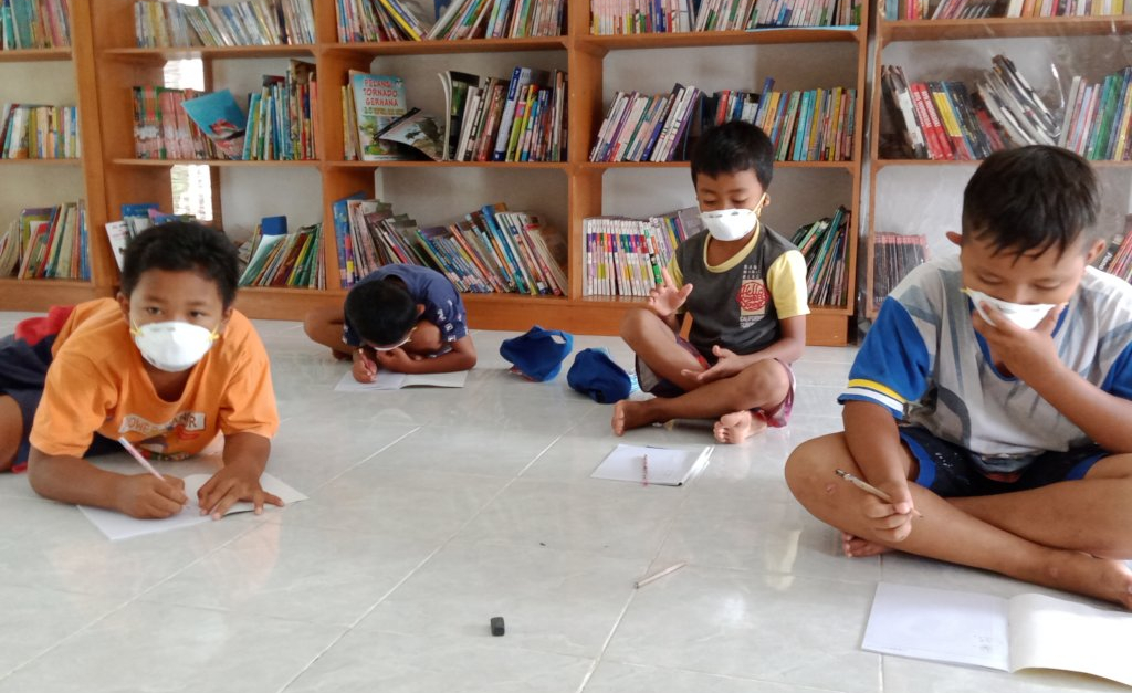 Students wearing masks doing school work in a small tutoring session in Indonesia
