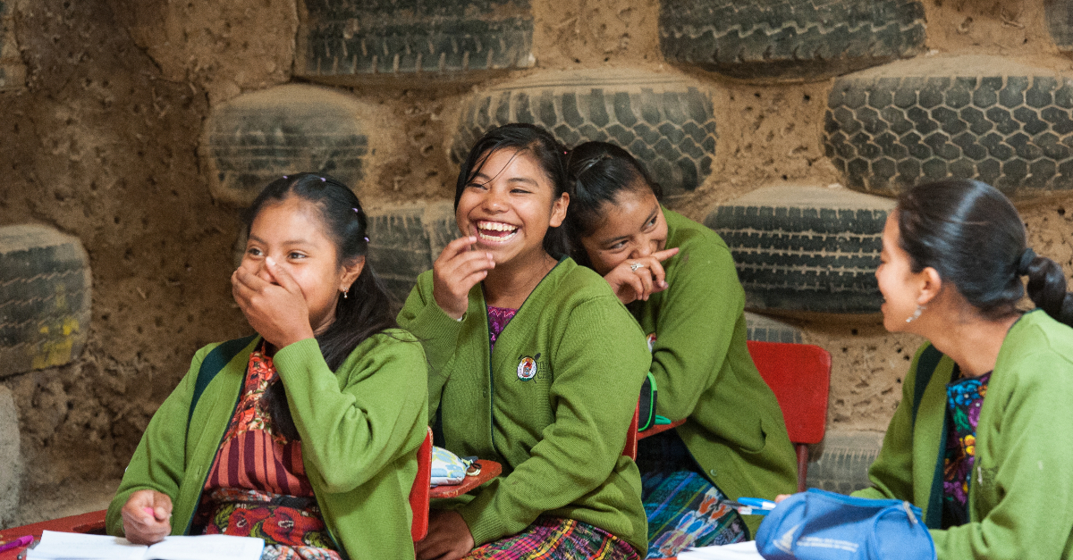 Four female students in green sweaters laugh with each other in a classroom made from tires and mud.