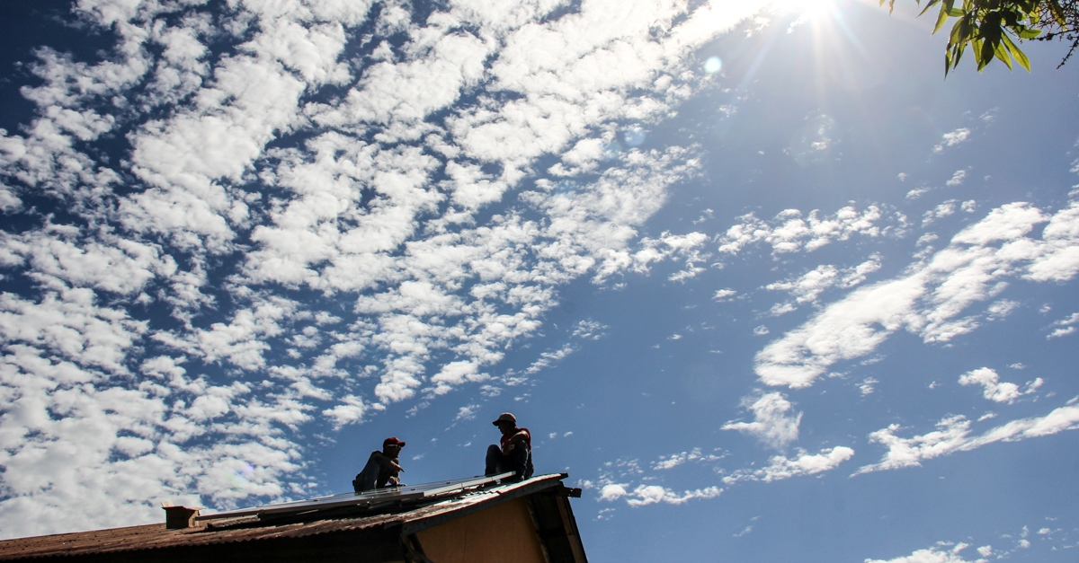 A photo of the sky with two people on the roof enjoying the clean air to introduce facts about air pollution