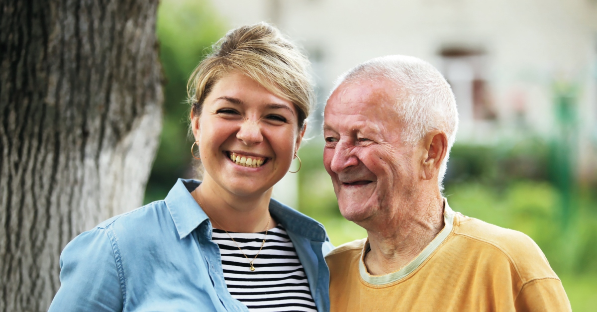 A woman in a black and white striped shirt smiles as she embraces an elderly man in a yellow shirt. creative Father's Day gift