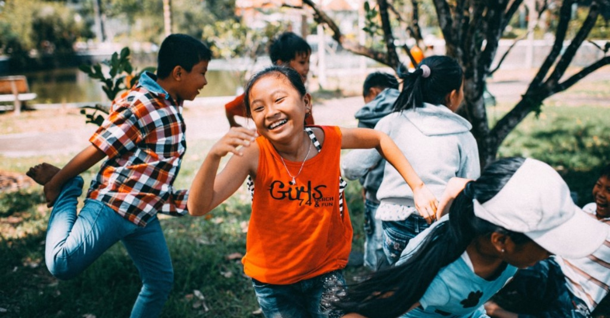 A girl in an orange tanktop smiles as she plays tag with other children.