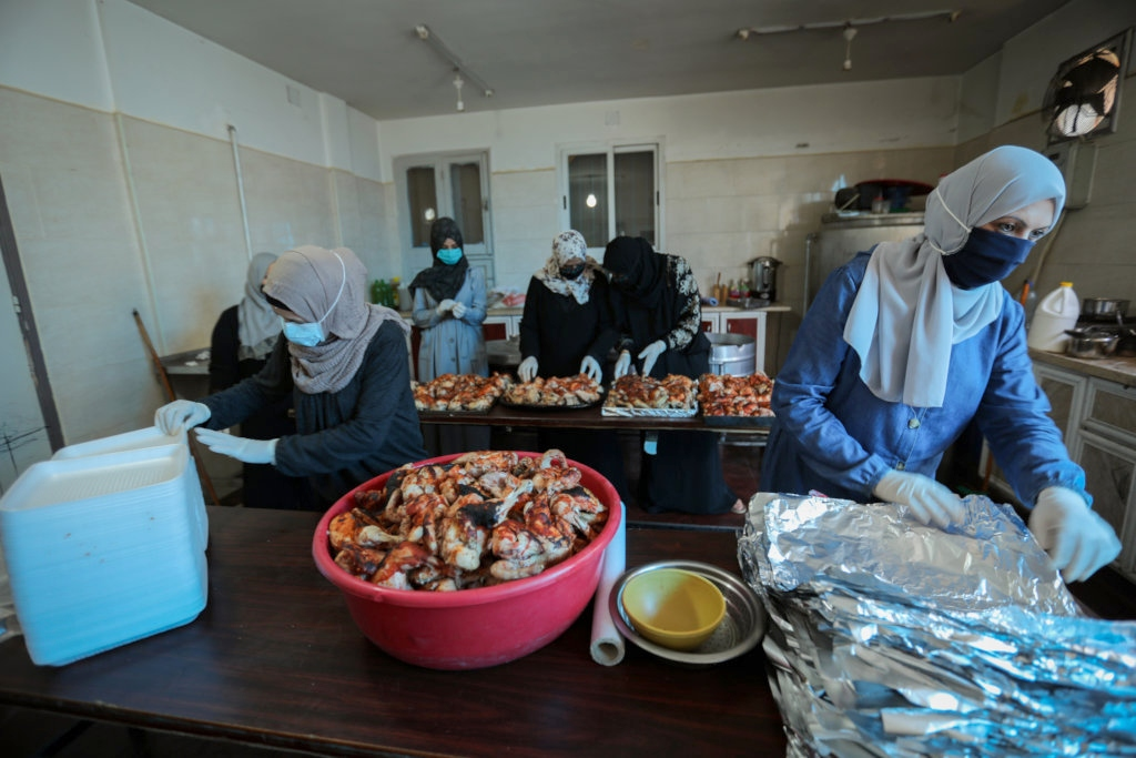 Women in gloves and hijabs prepare to package chicken in aluminum foil for delivery