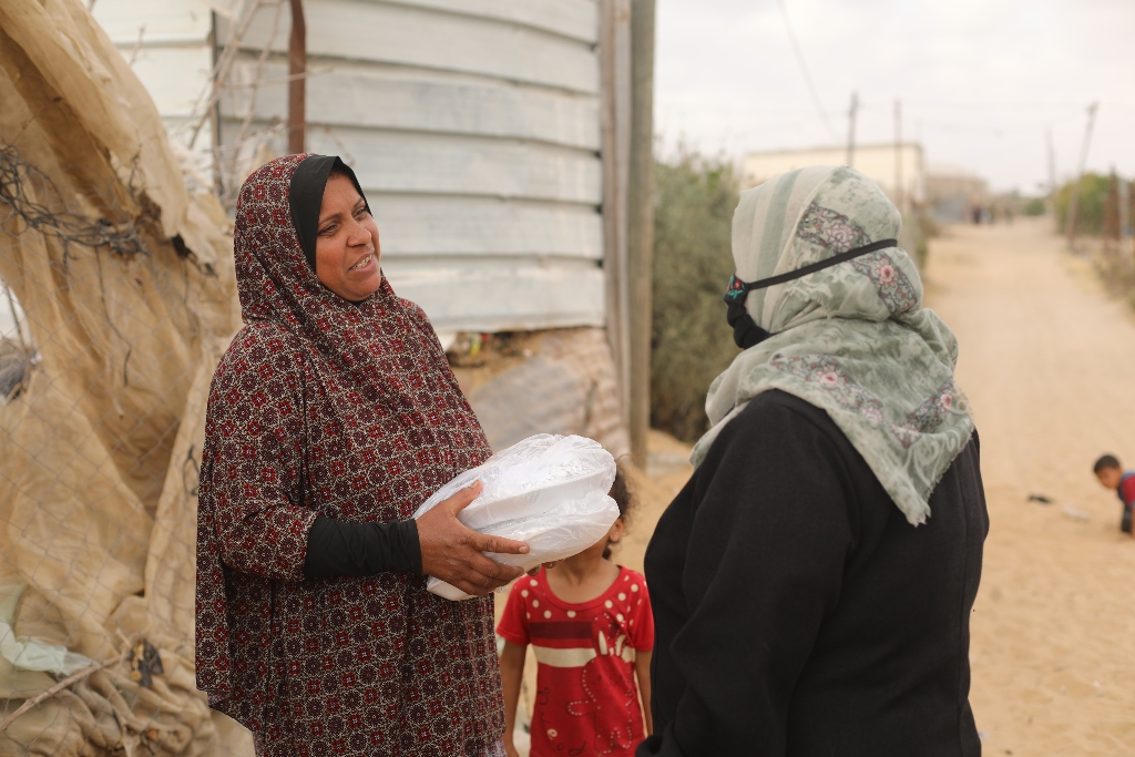 A woman with a young girl at her side smiles as she receives two containers of food from Mrs. Najah.