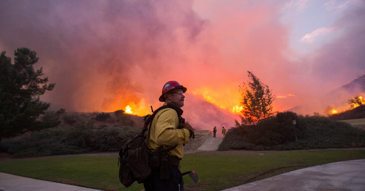 A firefighters stands with pink and orange flames behind him in the distance at the Blue Ridge Fire in Yorba Linda