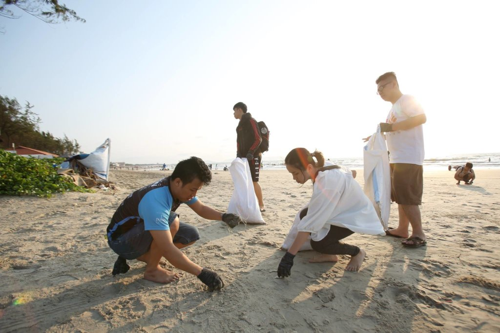 Young people pick up trash on a beach with the sun shining behind them
