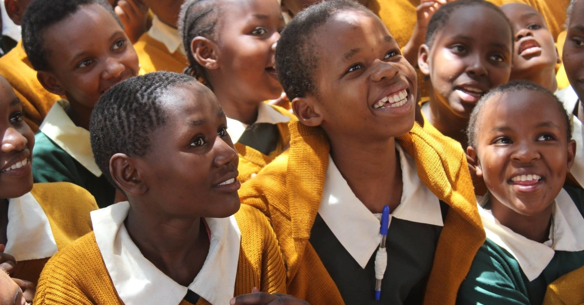 A group of children in green school uniforms and yellow cardigans look up, smiling