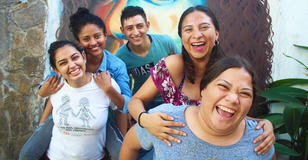 Young people smile in front of a wall mural of a woman's face