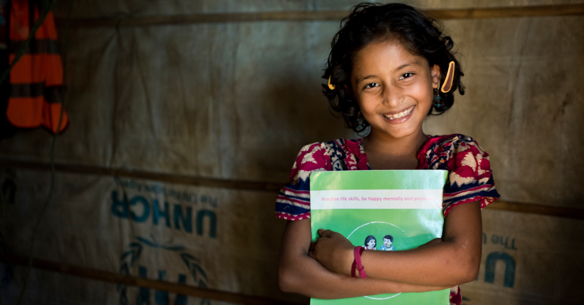 Smiling girl holds a book.