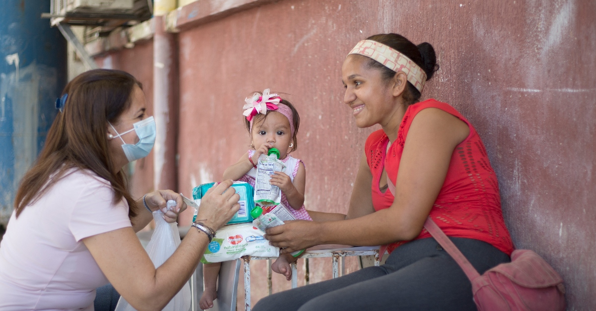 A woman and her young daughter receive children's aid supplies from Friends of the Children of Venezuela worker