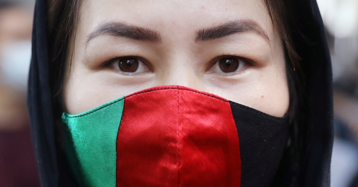 A woman wearing a face mask with the colors of Afghanistan's flag looks straight ahead.